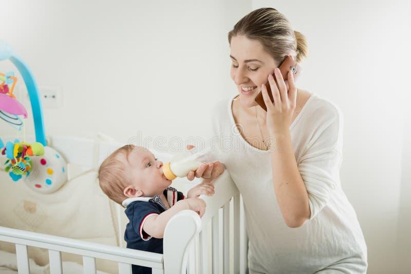 Ståenden av att le den unga affärskvinnan som talar vid telefonen och matar hennes litet, behandla som ett barn sonen arkivfoto