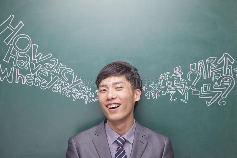 Ståenden av att le den unga affärsmannen framme av det svarta brädet med kinesiskt och engelska skriver att komma från varje öra arkivfoton