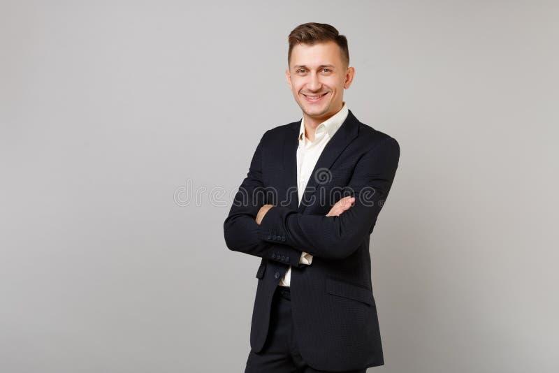 Ståenden av att le den unga affärsmannen i klassiska svarta dräkt- och skjortainnehavhänder vek isolerat på den gråa väggen royaltyfria bilder