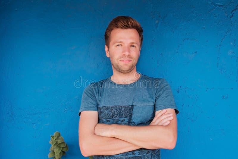 Ståenden av att le den unga caucasian mannen som står nära den blåa väggen med, freen bladet royaltyfri bild