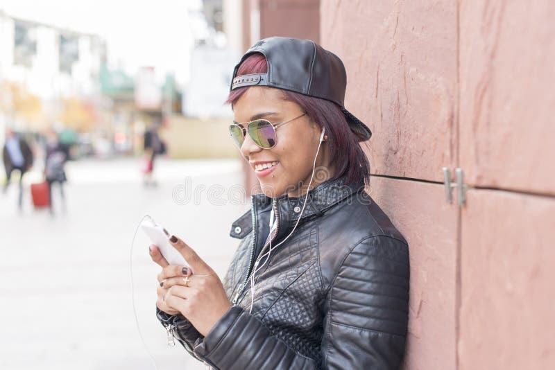 Ståenden av att le den unga kvinnan med hörlurar och ilar lyssnande musik för telefon i gatan royaltyfri foto