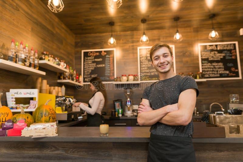 Ståenden av att le den unga manliga coffee shopägaren, den säkra kvinnan med armar korsade att stå på räknaren med baristaarbete  royaltyfria bilder