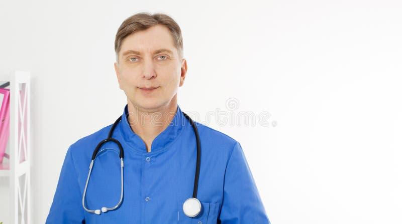 Ståenden av att le doktorn som poserar med kontoret, bär han en stetoskop, kopieringsutrymme för logo eller text royaltyfri fotografi