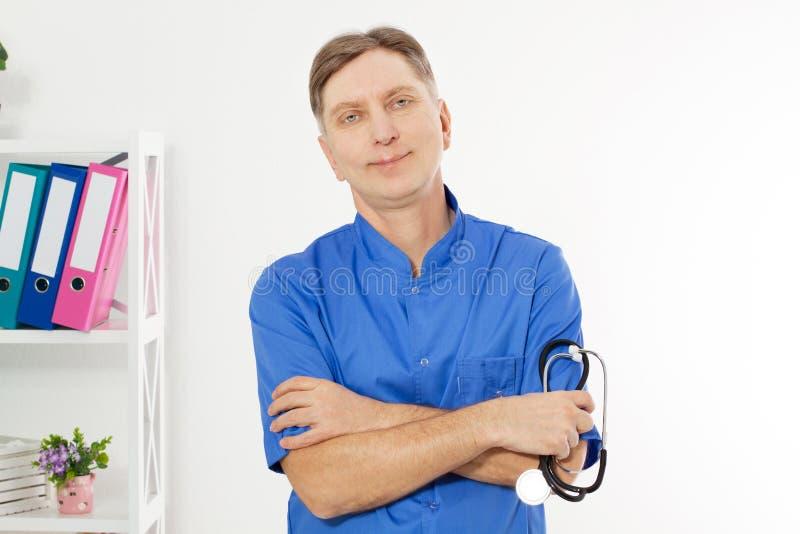 Ståenden av att le doktorn som poserar med kontoret, ska han rymma en stetoskop, kopieringsutrymme för logo eller text fotografering för bildbyråer