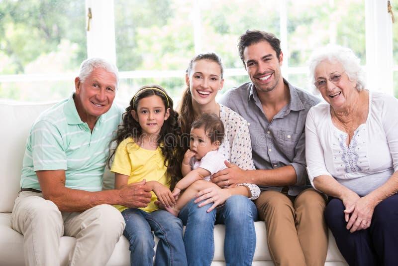 Ståenden av att le familjen med behandla som ett barn, medan sitta på soffan arkivbild