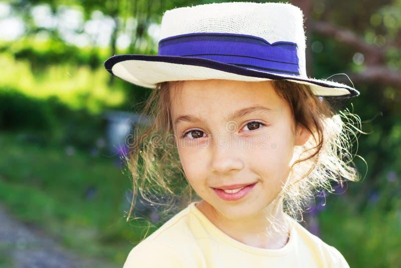 Ståenden av att le härligt tonårs- i hatt, mot gräsplan av sommar parkerar royaltyfri foto