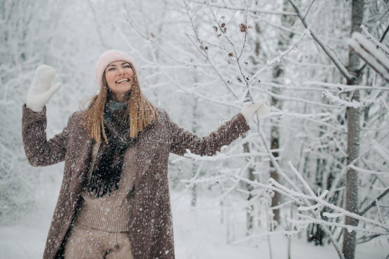 Ståenden av att le kvinnan i hatt går på i vinterskog arkivfoton