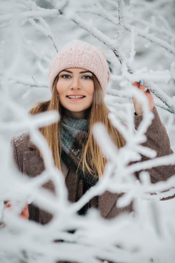 Ståenden av att le kvinnan i hatt går på i vinterskog royaltyfri foto