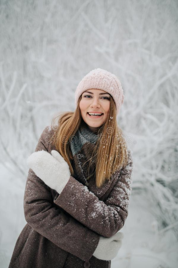 Ståenden av att le kvinnan i hatt går på i vinterskog royaltyfria bilder