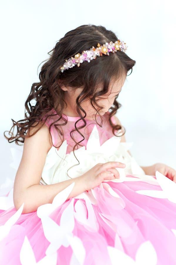Ståenden av att le lilla flickan i prinsessarosa färger klär med fjärilar arkivfoton
