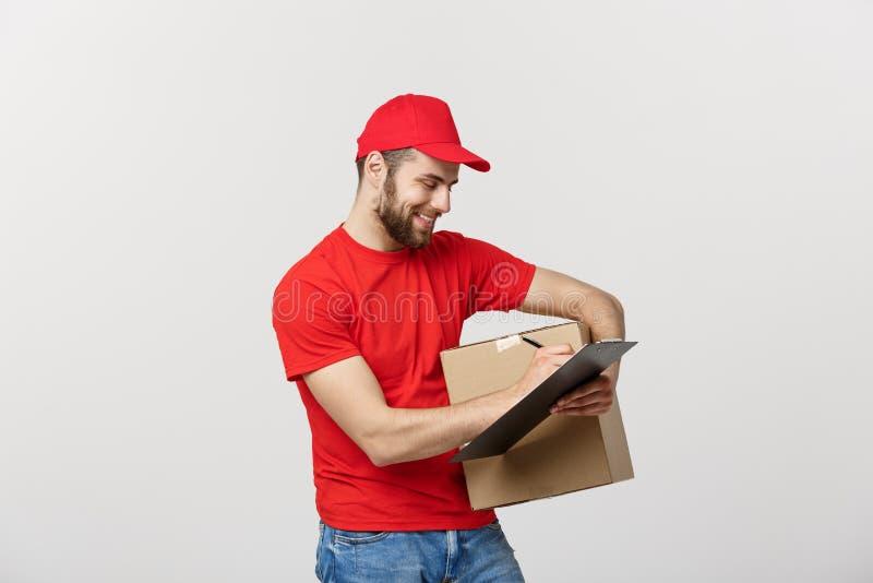 Ståenden av att le manlig handstil för leveransmannen på skrivplattan och innehavet boxas Isolerat över vitbakgrund royaltyfri foto