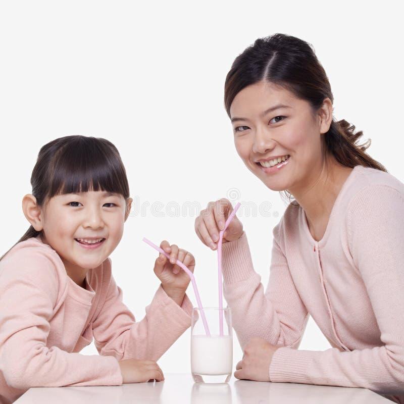 Ståenden av att le moder- och dottersammanträde på en tabell och att dela ett exponeringsglas av mjölkar med sugrör, studioskott royaltyfria bilder