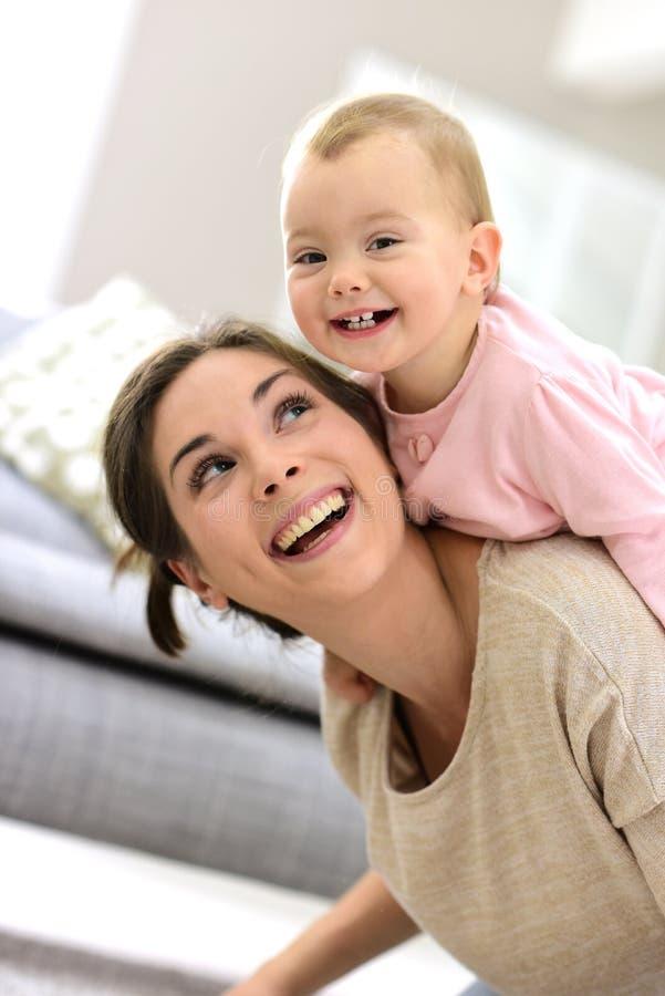 Ståenden av att le modern och behandla som ett barn flickan royaltyfria foton