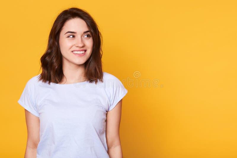 St?enden av attraktivt h?rligt ganska haired posera f?r ung dam som isoleras ?ver gul bakgrund som ?t sidan ser, ser dr?mlik och arkivfoton