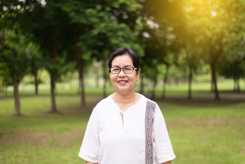 Ståenden av bärande exponeringsglas för den höga asiatiska kvinnan som visar tummen på allmänhet, parkerar upp och lyckligt och l royaltyfria foton