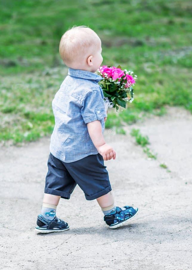 Ståenden av baksida av litet behandla som ett barn pojken som går med härliga rosor som buketten som är utomhus- på sunner, parke arkivfoto