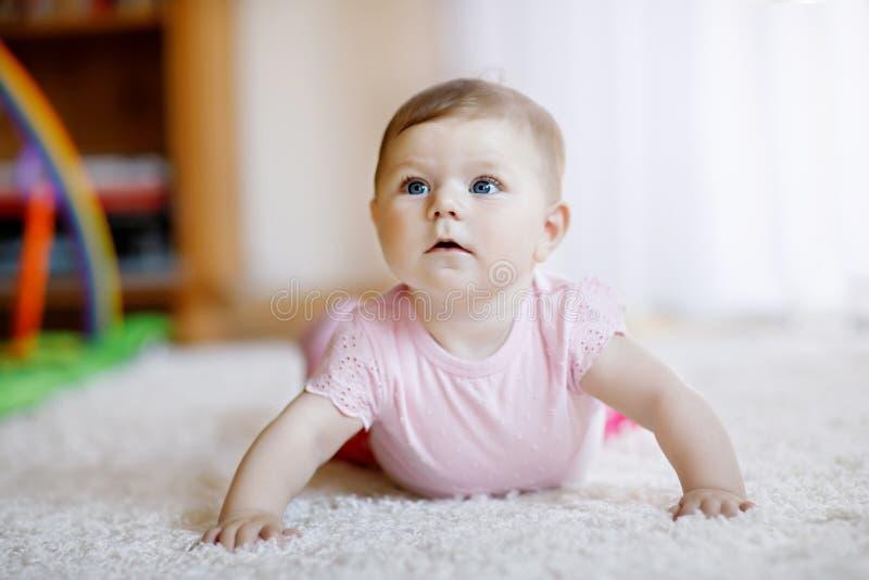 Ståenden av behandla som ett barn flickan i det vita soliga sovrummet Nyfött barn som lär att krypa Barnkammare för barn Textil o arkivbild
