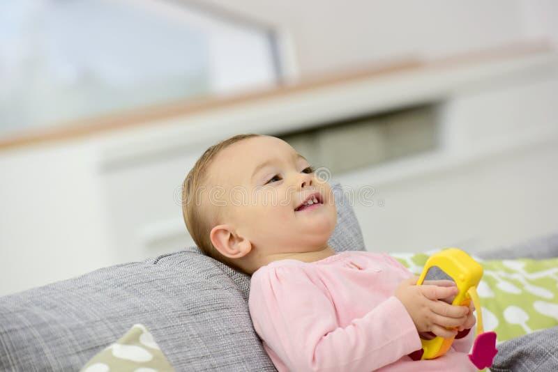 Ståenden av behandla som ett barn flickan som ligger på soffan royaltyfri fotografi
