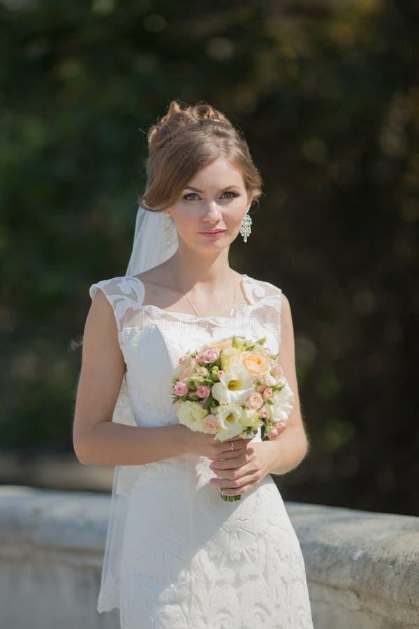 Ståenden av bruden med buketten parkerar in royaltyfria bilder