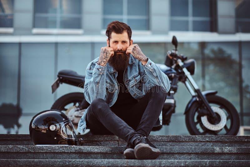 Ståenden av brutal skäggig manlig iklädd jeans klår upp sammanträde på moment nära hans specialtillverkade retro motorcykel royaltyfri fotografi