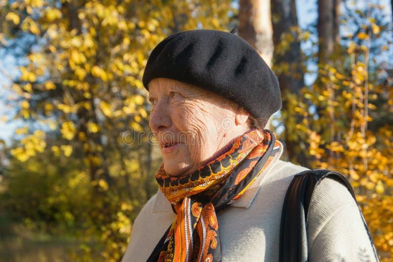 Ståenden av den äldre höga kvinnan i hatt på hösten parkerar fotografering för bildbyråer
