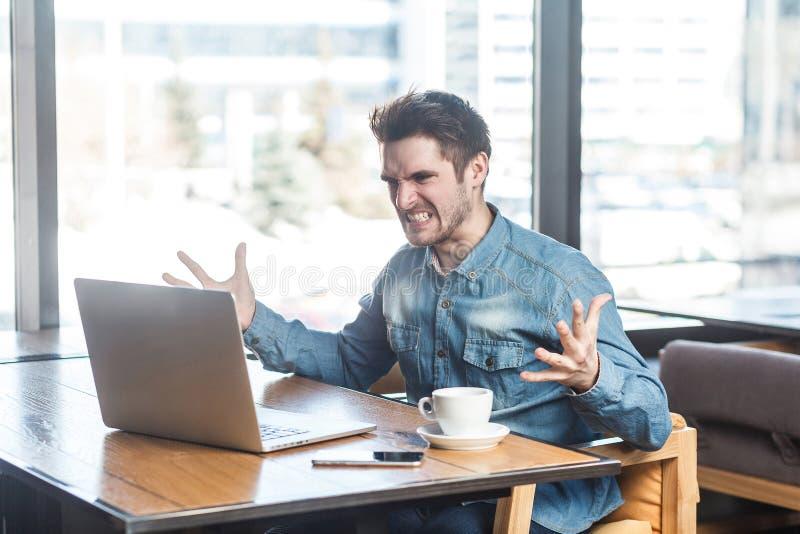 Ståenden av den aggressiva olyckliga unga affärsmannen i jeansskjorta sitter i kafé och har dåligt lynne arkivbild