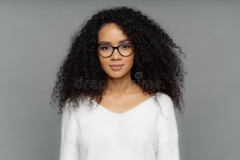 Ståenden av den allvarliga kvinnan med mörk hud, afro- buskigt hår, bär stora genomskinliga exponeringsglas, och den vita mjuka t royaltyfria foton