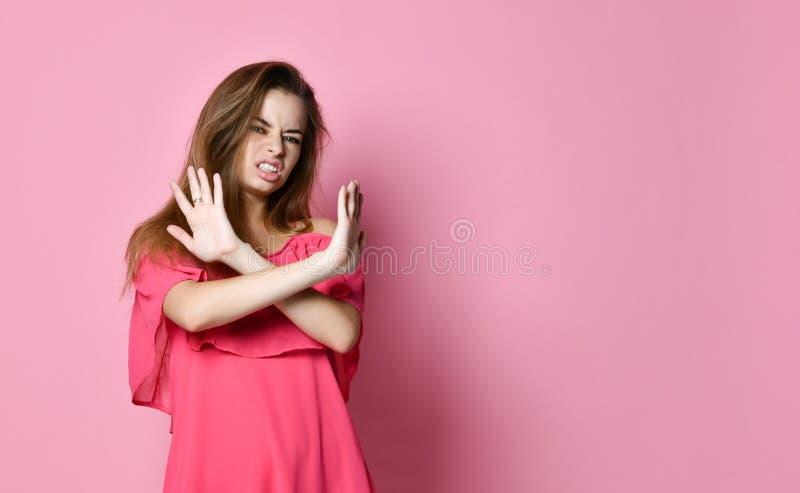 Ståenden av den allvarliga, olyckliga säkra blonda kvinnan som rymmer två armar, korsade och att göra en gest inget tecken, royaltyfri bild