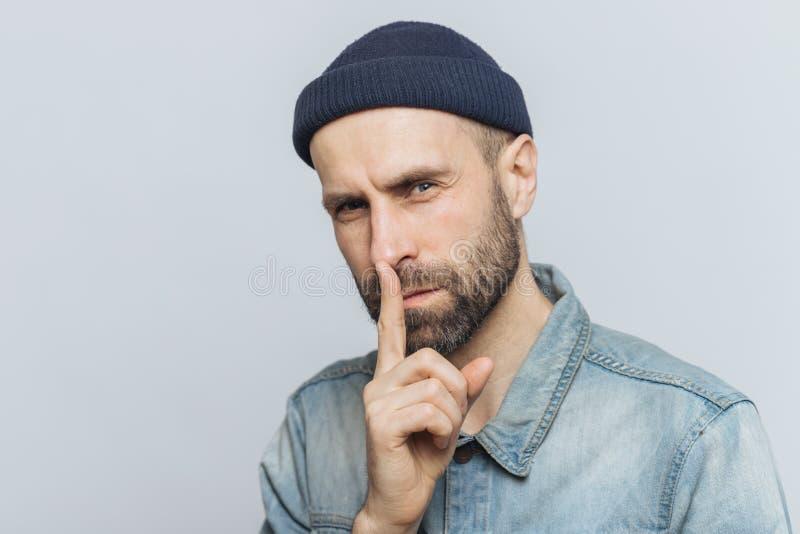 Ståenden av den allvarliga skäggiga mannen med attraktiv blick, främre finger för uppehällen på kanter, blickar med hemligt uttry royaltyfri bild