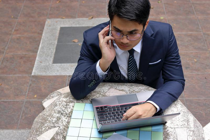 Ståenden av den allvarliga unga affärsmannen talar på telefonen för hans arbete i det utomhus- parkerar royaltyfri foto