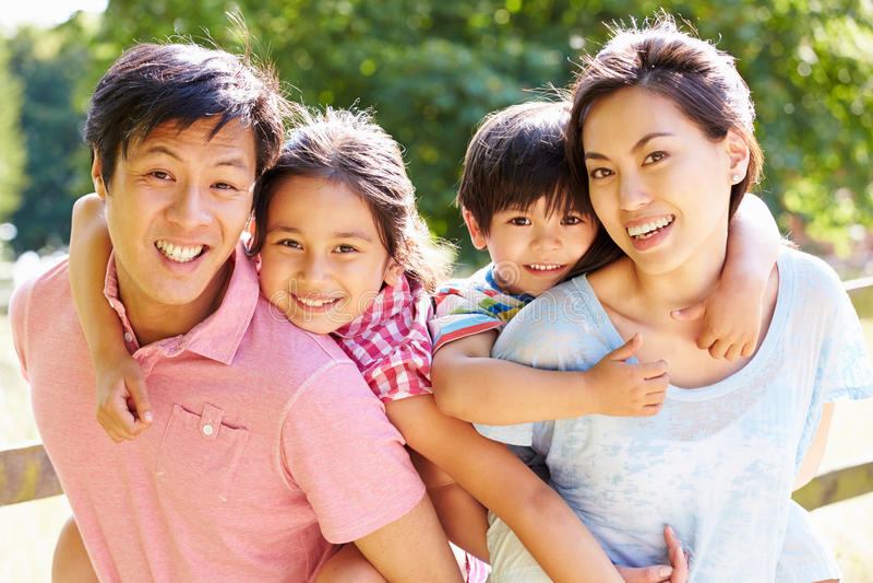 Ståenden av den asiatiska familjen som tycker om, går i sommarbygd arkivbilder
