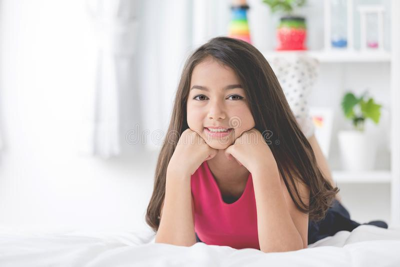 Ståenden av den asiatiska gulliga flickan vilar på sängen och att se en kamera arkivfoto