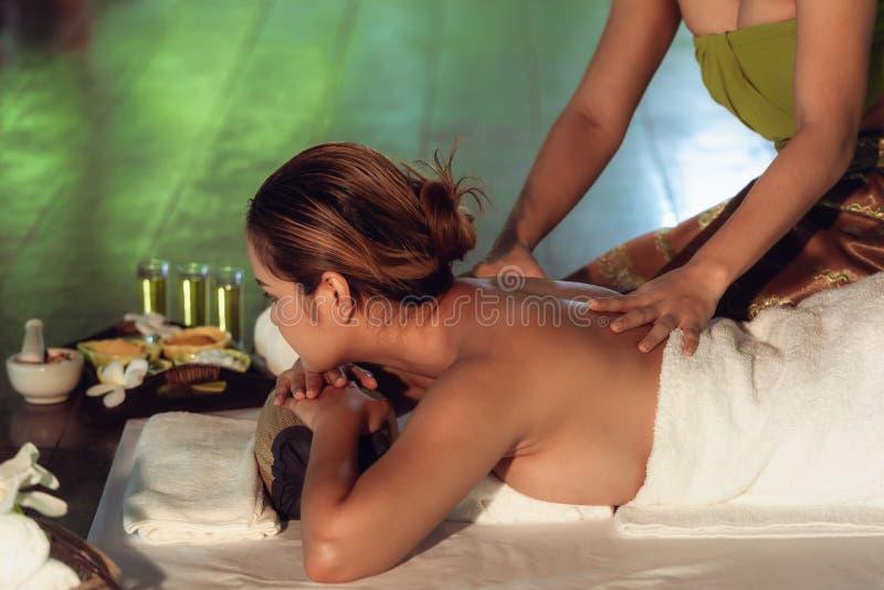 Ståenden av den asiatiska kvinnan är avslappnande i brunnsortmassage arkivbild