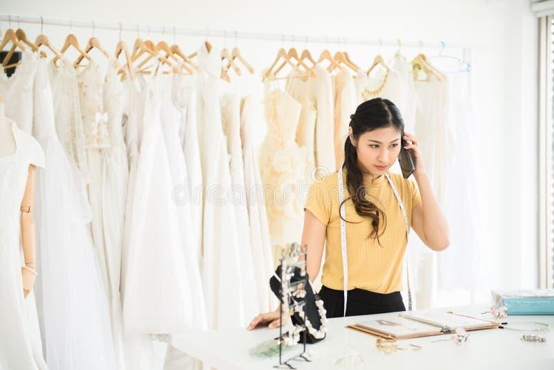 Ståenden av den asiatiska kvinnan som arbetar och använder mobilephonen i bröllopsklänninglager, den härliga sömmerskan shoppar i royaltyfria foton