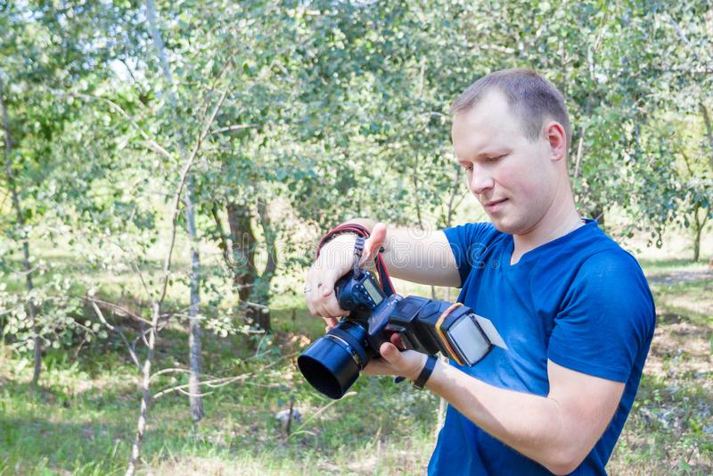 Ståenden av den attraktiva manliga fotografen på arbete ser till kameran field treen Ung man med en DSLR-kamera i händer En perso royaltyfria bilder