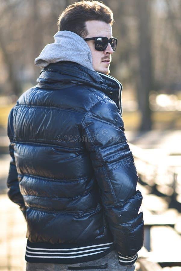 Ståenden av den attraktiva mannen i solglasögon med tillfällig kläder går i parkerar royaltyfri fotografi
