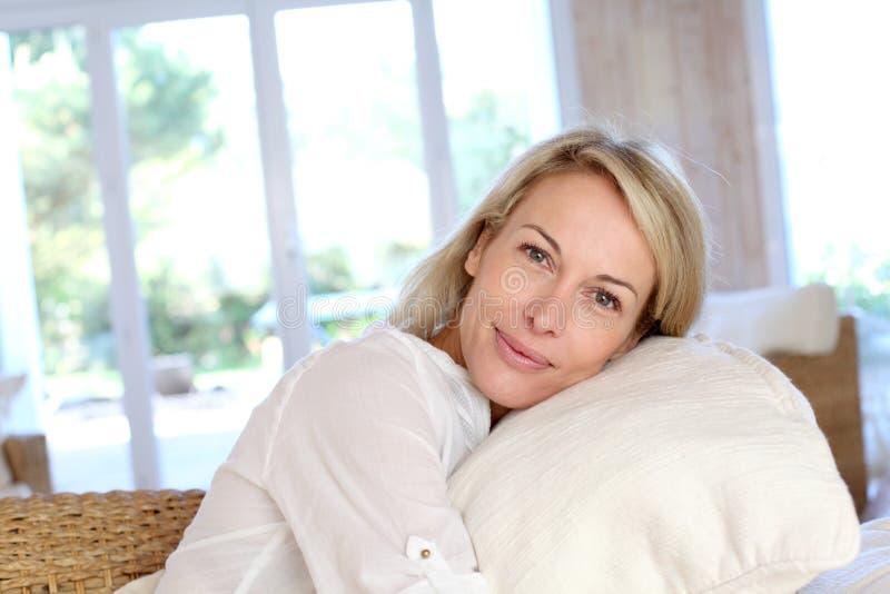 Ståenden av den blonda unga kvinnan i vit beklär att koppla av hemma royaltyfri fotografi