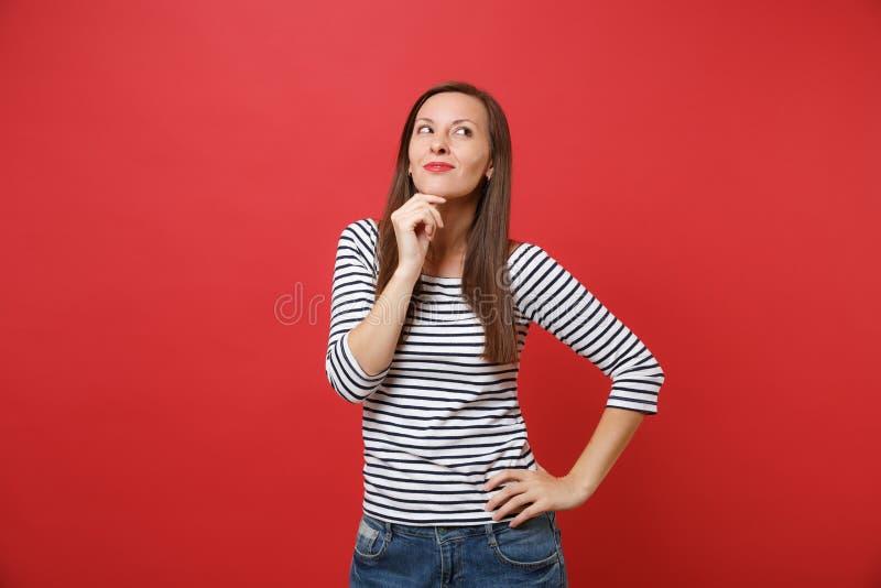 Ståenden av den drömlika le unga kvinnan i randig kläder som ser upp, satte upp handstöttan på hakan som isolerades på ljust rött arkivbilder