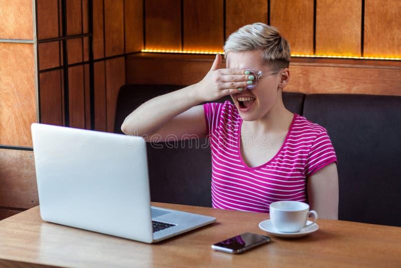 Ståenden av den emotionella förskräckta lyckliga unga affärskvinnan i rosa t-skjorta sitter i kafé och täcker ögonen till henne m arkivfoton