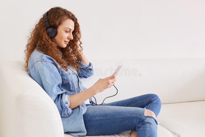 Ståenden av den förtjusta unga kvinnliga melomanen lyssnar favorit- musik via modernt ilar telefonen och hörlurar, iklädd fashion royaltyfria foton
