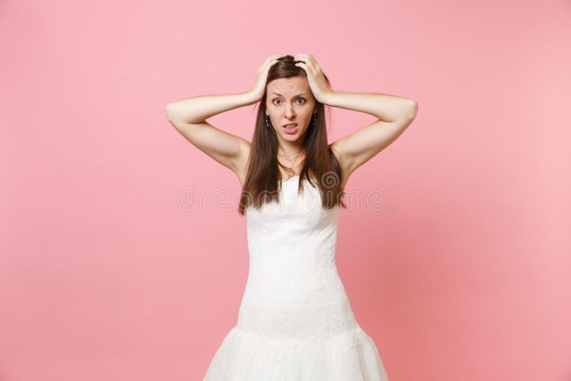 Ståenden av den förvirrade förbryllade bruden som kvinnan snör åt in den vita bröllopsklänningen oroar klamra sig fast intill huv fotografering för bildbyråer
