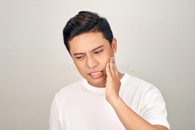 Ståenden av den feta asiatiska mannen att använda hans hand trycker på hans kind som känner sig smärtsam från tandvärk Muntligt v royaltyfria foton