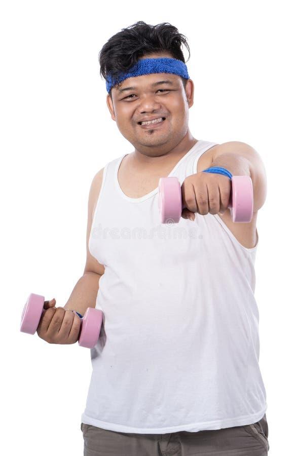 Ståenden av den feta unga mannen som gör övning med hantlar, gör stansmaskin arkivfoto