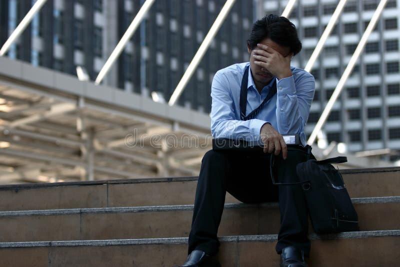 Ståenden av den frustrerade unga asiatiska affärsmannen tar av exponeringsglas och stänger hans ögon han känner belastning eller  royaltyfria bilder