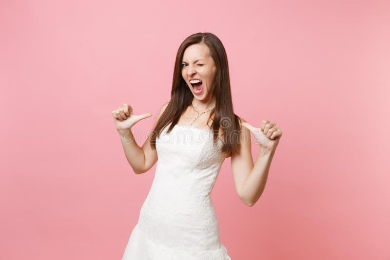 Ståenden av den galna brudkvinnan i härligt snör åt den vita bröllopsklänningen som skriker att blinka och att peka tummar på hen arkivbilder