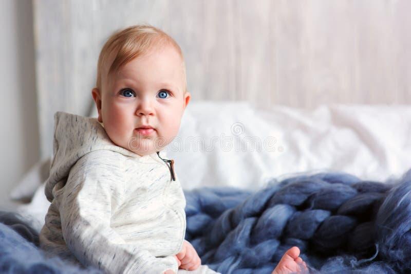 Ståenden av den gamla gulliga 8 månaden behandla som ett barn flickasammanträde på sängen på stack filten i storformat royaltyfria bilder