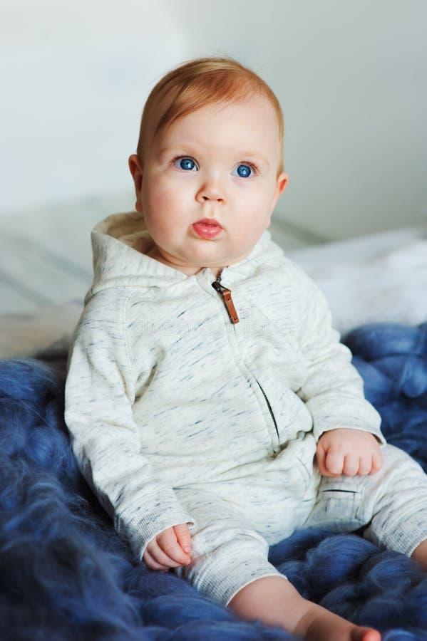 Ståenden av den gamla gulliga 8 månaden behandla som ett barn flickasammanträde på sängen på stack filten i storformat arkivfoto