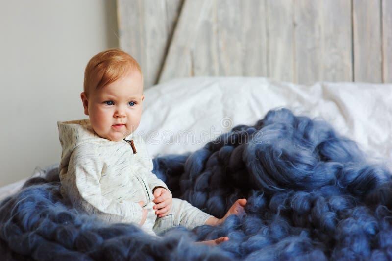 Ståenden av den gamla gulliga 8 månaden behandla som ett barn flickasammanträde på sängen på stack filten i storformat royaltyfria foton