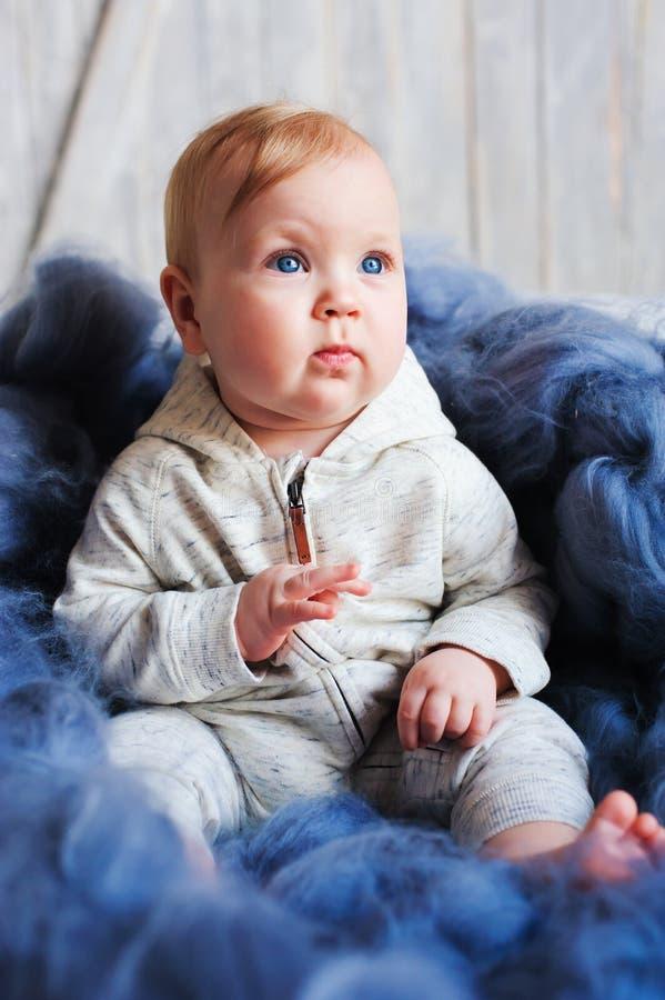 Ståenden av den gamla gulliga 8 månaden behandla som ett barn flickasammanträde på sängen på stack filten i storformat royaltyfri foto