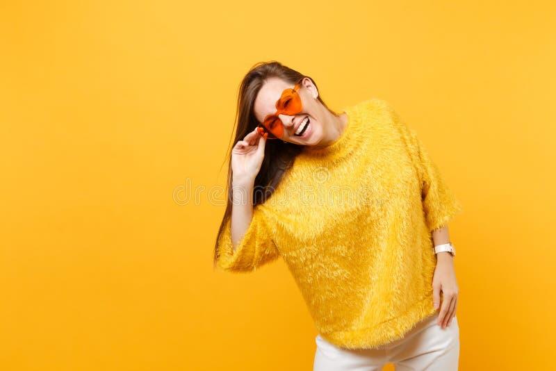 Ståenden av den glade lyckliga unga kvinnan i pälströja, vita flåsanden som rymmer orange exponeringsglas för hjärta, står isoler royaltyfri fotografi